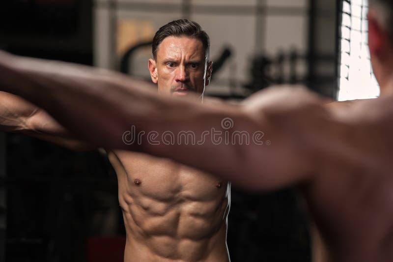 Vorbildliche Aufstellung der muskulösen Eignung hemdlos in der Turnhalle stockbild