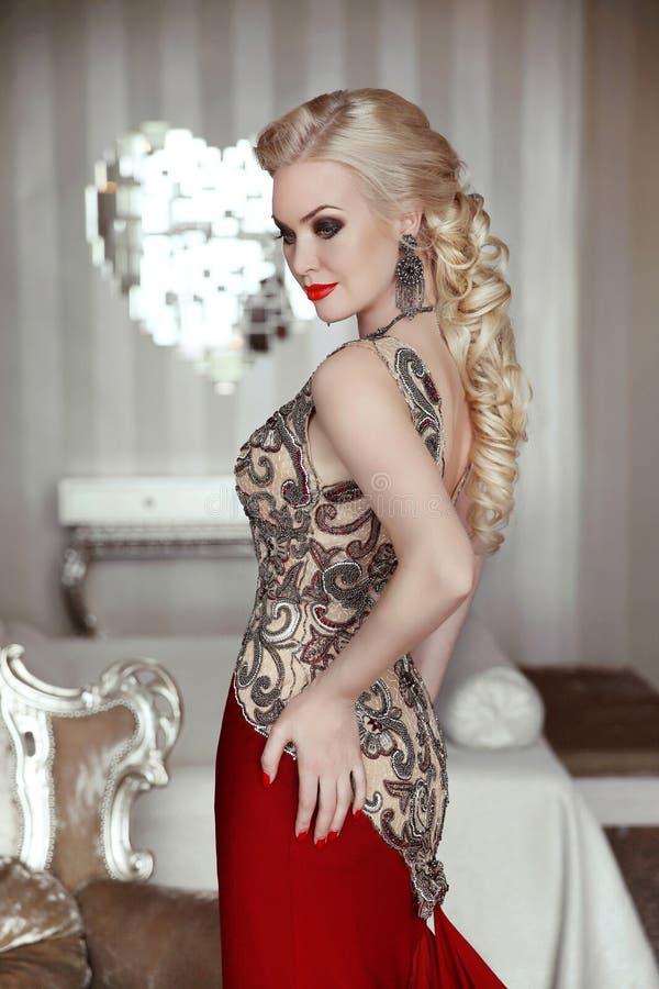 Vorbildliche Aufstellung der schönen blonden Frau im eleganten Kleid mit Make-up lizenzfreie stockfotografie