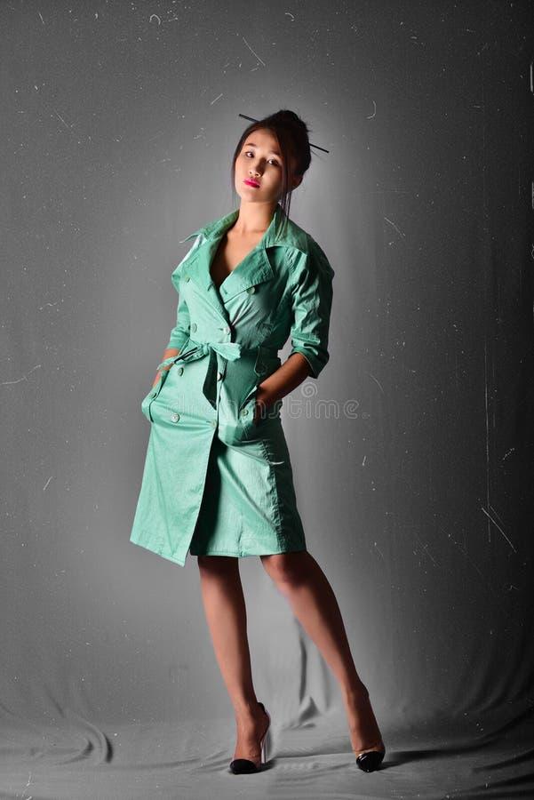 Vorbildliche Aufstellung im hellgrünen Regenmantel, der im Studio steht Retro- Art stockfotos