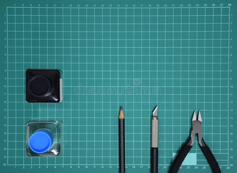 Vorbildliche Tool-Kit-Plastiktinte der Draufsicht, Kunstmesser, Zangen auf dem Schnitt des Platten- und Kopienraumes schneiden stockfoto