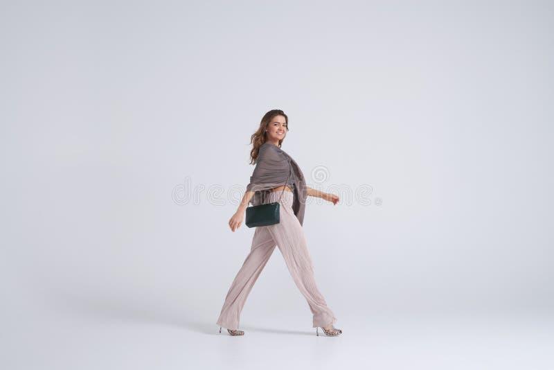 Vorbildliche tragende Tendenzkleidung, die gegen Hintergrund geht stockbilder