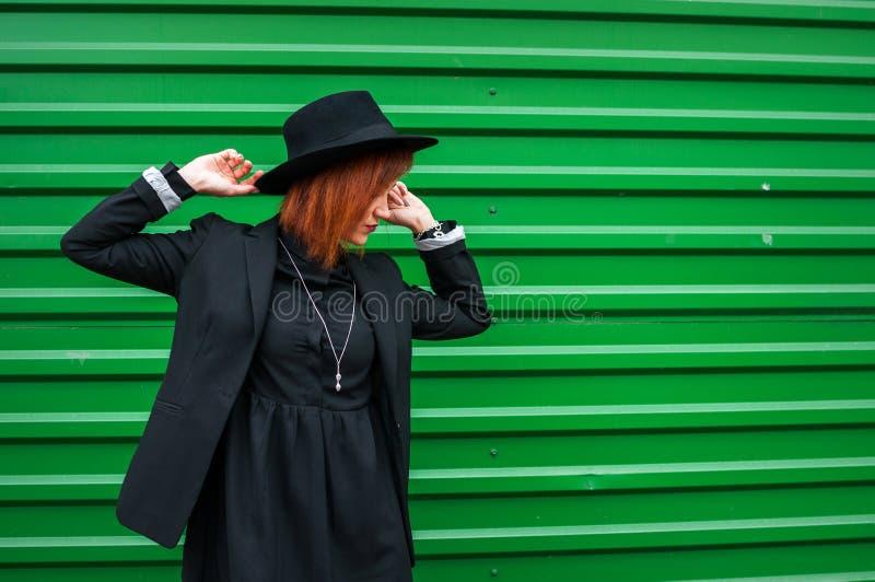 Vorbildliches Anziehen der attraktiven Mode im Freien durch die grüne Wand Stadtart Art und Weisefoto lizenzfreies stockbild
