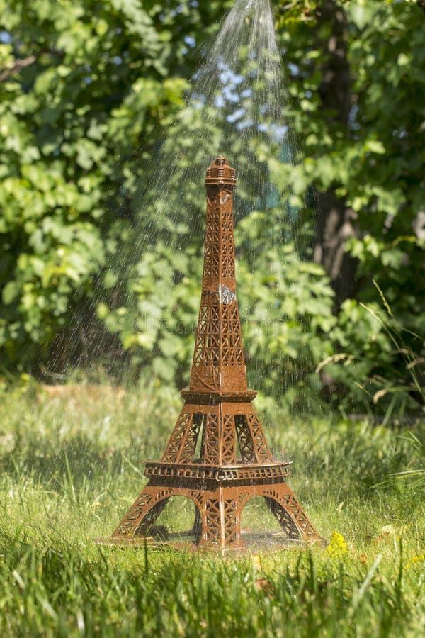 Vorbildliches Eiffel Tower der Pappe auf grünem Gras unter einem Strom des Wassers lizenzfreies stockbild