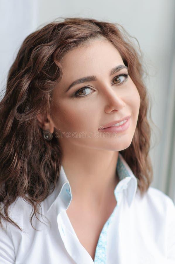 Vorbildliches Frauenporträt der Schönheit mit gelocktem braunhaarigem stockbild