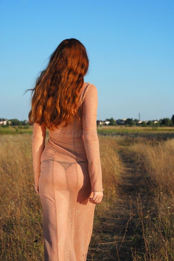 Vorbildliches Gehen auf Pfad im langen beige Kleid, hintere Ansicht stockbilder