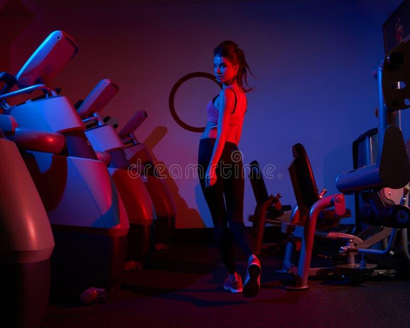 Vorbildliches Gehen der weiblichen Eignung zwischen zwei Reihen von Übung machin lizenzfreies stockfoto