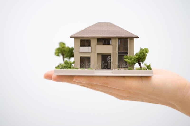 Vorbildliches Haus mit einer Hand lizenzfreie stockfotografie