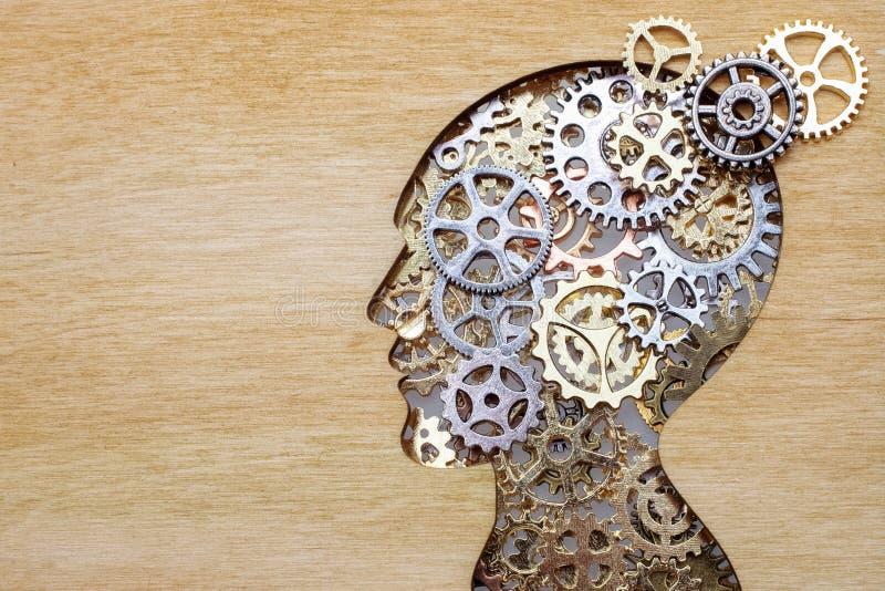 Vorbildliches Konzept des Gehirns gemacht von den Gängen und von den Zahnrädern auf hölzernem Hintergrund stockbild