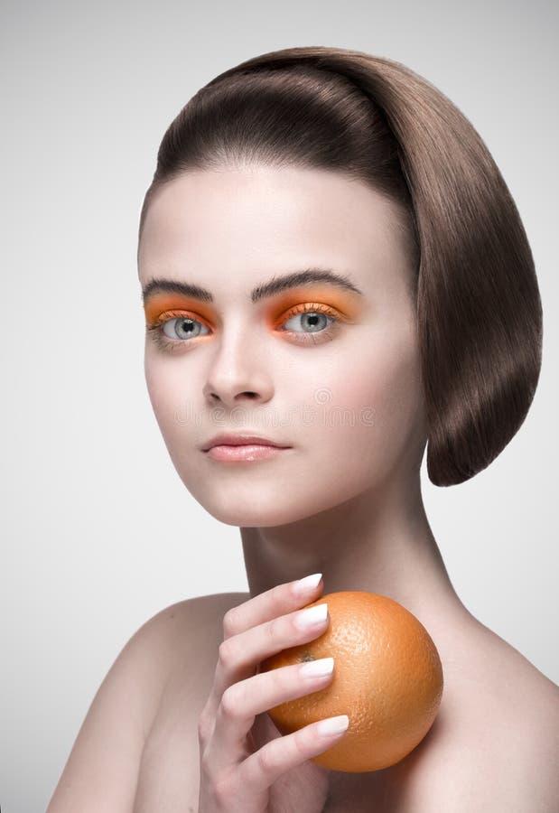 Vorbildliches Mädchen der Schönheit nimmt saftige Orangen Schönheit, helles Make-up lizenzfreie stockfotos