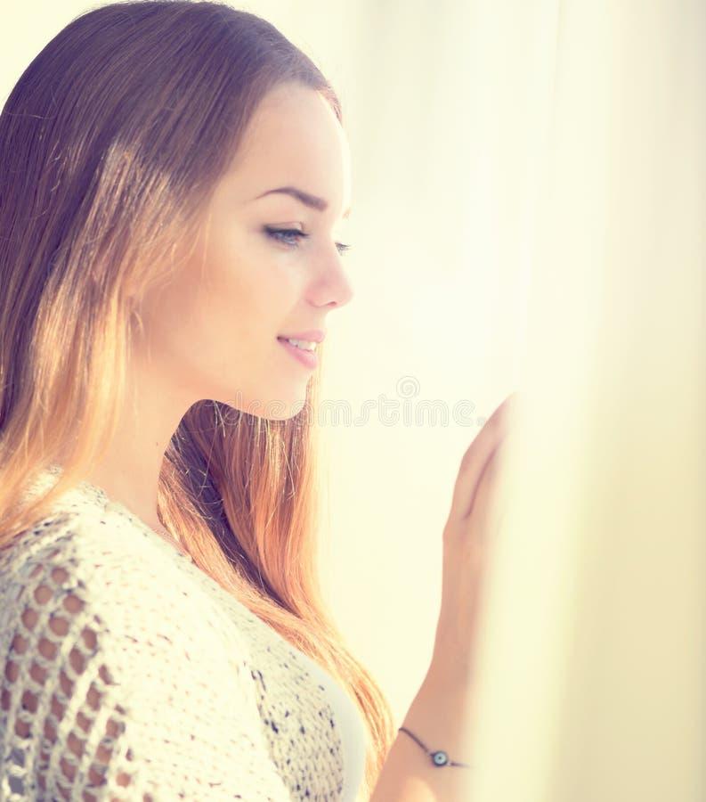 Vorbildliches Mädchen der Schönheit, welches heraus das Fenster schaut stockbild