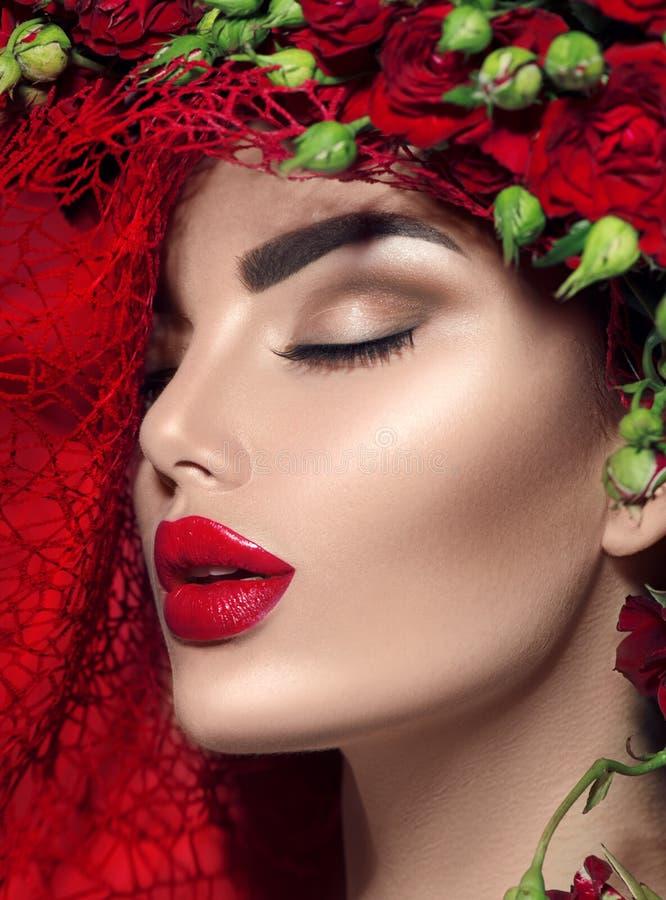 Vorbildliches Mädchen mit roten Rosen blühen Kranz und Modemake-up Blüht Frisur lizenzfreie stockfotografie