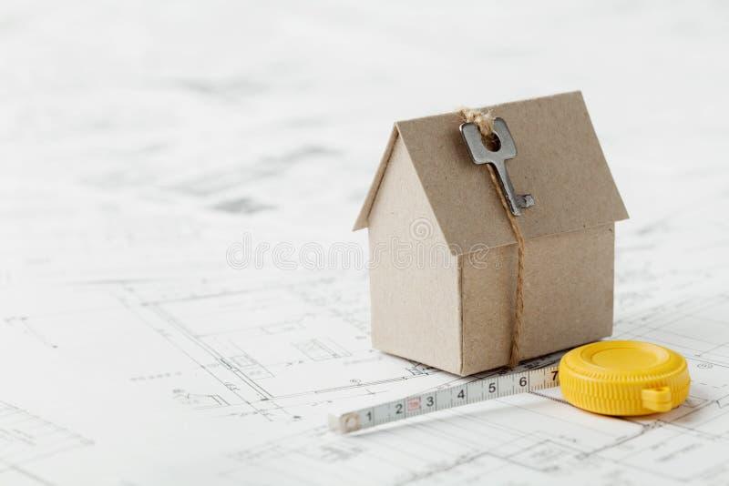 Vorbildliches Papphaus mit Schlüssel und Maßband auf Plan Wohnungsbau-, Architektur-und BauKonzept des Entwurfes stockfoto
