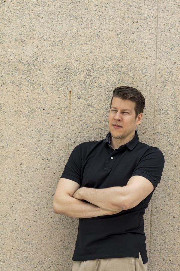 Vorbildliches Portrait Pose Leaning auf beige Wand im Freien lizenzfreies stockfoto