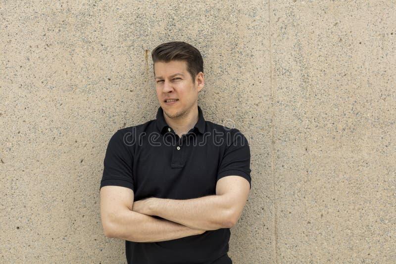 Vorbildliches Portrait Pose Leaning auf beige Wand im Freien lizenzfreie stockbilder