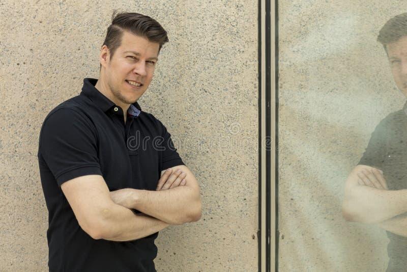 Vorbildliches Posing vor beige Wand und Fenster im Freien lizenzfreie stockfotos