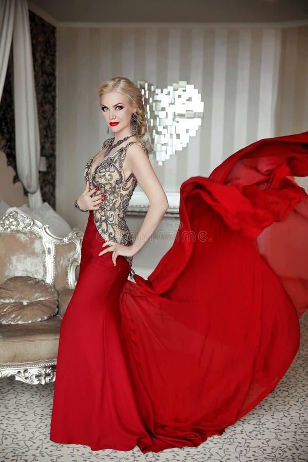 Vorbildliches Tragen der attraktiven blonden Frau im eleganten Kleid mit blowi stockbilder