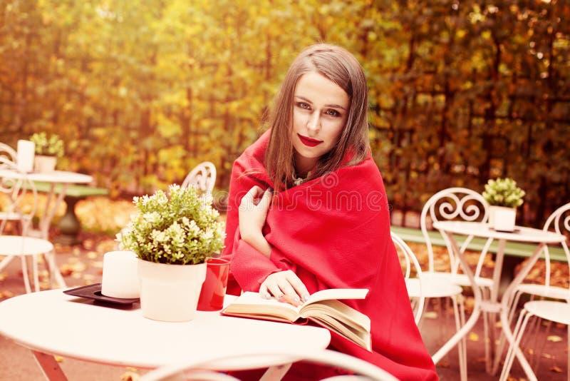 Vorbildliches Woman Reading ein Buch in einem Café draußen lizenzfreies stockfoto