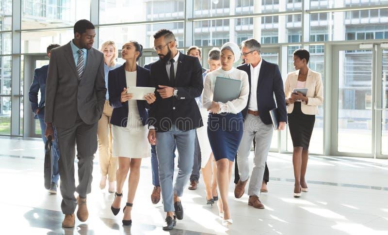 Vorderansicht der Gruppe verschiedener Geschäftsleute, die zusammen in Lobbybüro gehen lizenzfreie stockfotos