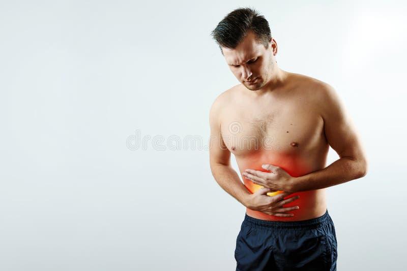 Vorderansicht, der Mann hält seine Hände zum Magen, Bauchschmerzen, Schmerz im Magen hervorhob im Rot stockfoto