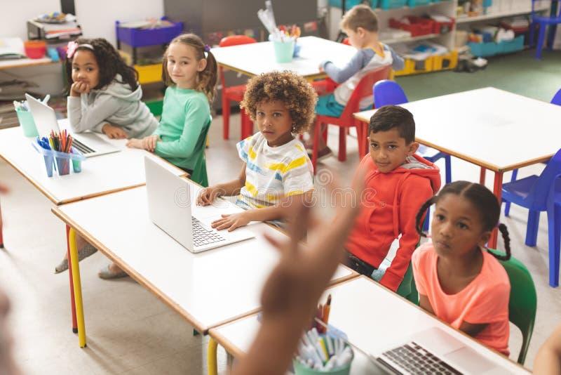 Vorderansicht der Reihe hörenden Schulkinder ihr der Lehrer stockbilder