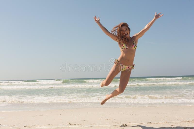 Vorderansicht der schönen jungen kaukasischen Frau im Bikini, der auf den Strand springt stockfoto
