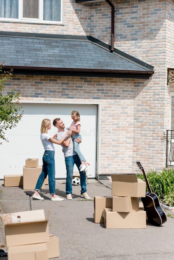 Vorderansicht der Stellung des glücklichen Paars mit Tochter auf Händen vor neuem stockfotografie