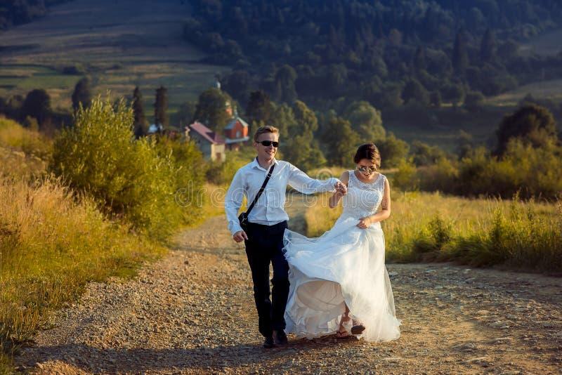 Vorderansicht des attraktiven jungen Jungvermähltenpaarhändchenhaltens, lächelnd und aktiv gehen entlang die Straße in lizenzfreie stockfotos