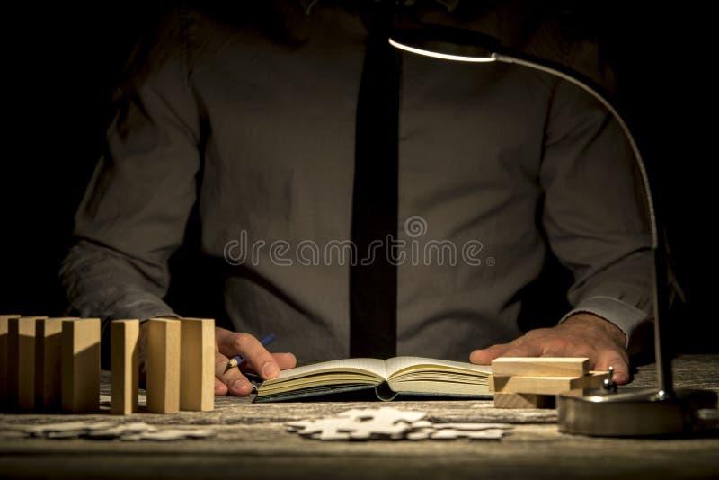 Vorderansicht des Geschäftsmannes die späten Stunden bearbeitend, die an seinem offi sitzen lizenzfreie stockfotos