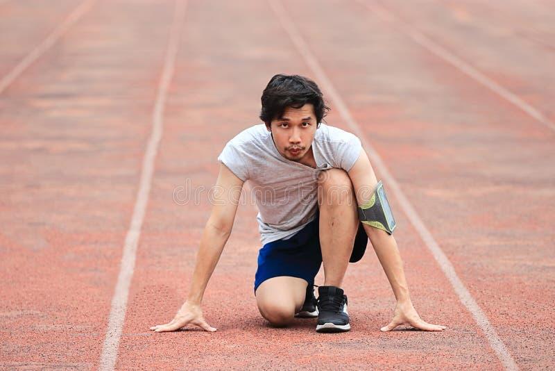 Vorderansicht des jungen asiatischen Athletenmannes bereit, auf Bahn im Stadion zu laufen Gesundes Konzept stockbilder