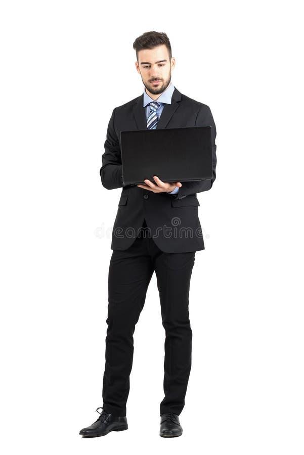 Vorderansicht des jungen bärtigen Unternehmensmannes, der an Laptop arbeitet stockfoto