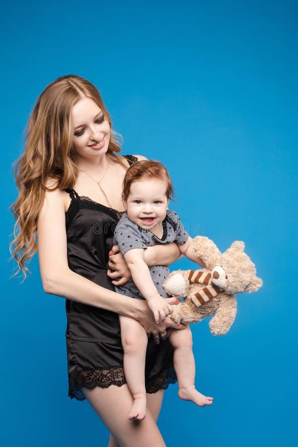 Vorderansicht des positiven kleinen Babys, das mit Mutter lacht lizenzfreies stockfoto