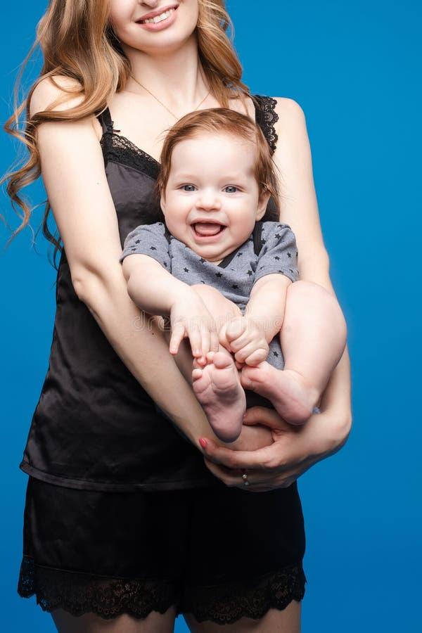 Vorderansicht des positiven kleinen Babys, das mit Mutter lacht stockfotos