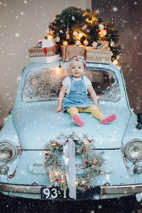 Vorderansicht des süßen und modernen kleinen netten Mädchens, das auf dem blauen Retro- Auto verziert für Weihnachten sitzt stockfotografie