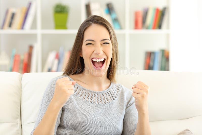 Vorderansicht einer aufgeregten Frau, die zu Hause Kamera betrachtet lizenzfreie stockbilder