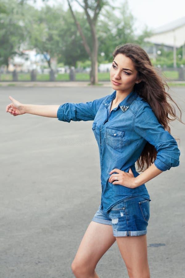 Vorderansicht einer jungen Frau, die auf Stadtstraße per Anhalter fährt stockfoto