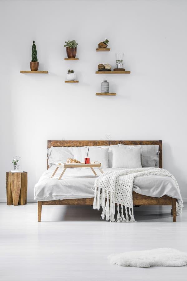 Vorderansicht eines hölzernen gestalteten Doppelbetts mit Leinen, Kissen und stockbild