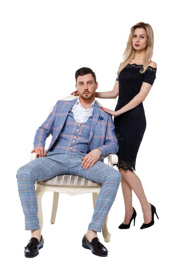 Vorderansicht eines Luxuspaares Ein Mann sitzt auf einem teuren Stuhl, eine Frau in einem Kleid steht nahe bei ihm stockfotografie