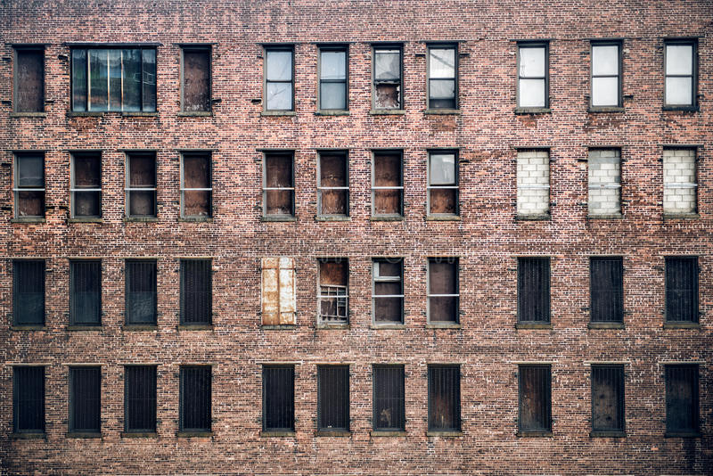 Vorderansicht von Fenstern eines verschalten-oben verlassenen Ziegelsteinwolkenkratzer-Gebäudes von der Straße in New York City stockfotos