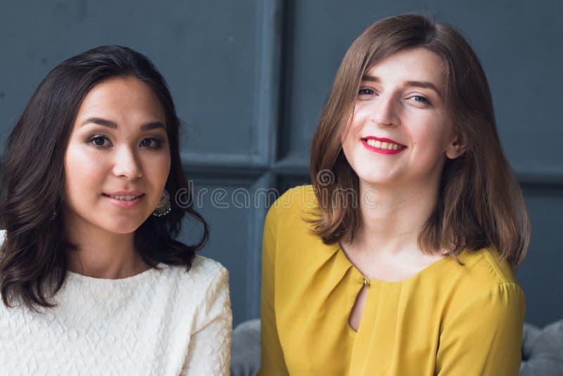 Vorderansicht von zwei lächelnden jungen Freundinnen, die zu Hause im Wohnzimmer sitzen stockfoto