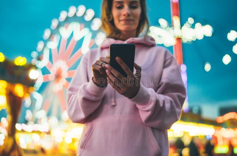 Vorderansichtmädchen, das Finger auf Schirm Smartphone auf defocus Hintergrund bokeh Licht in der Abendstraßenanziehungskraft, Fr stockfoto