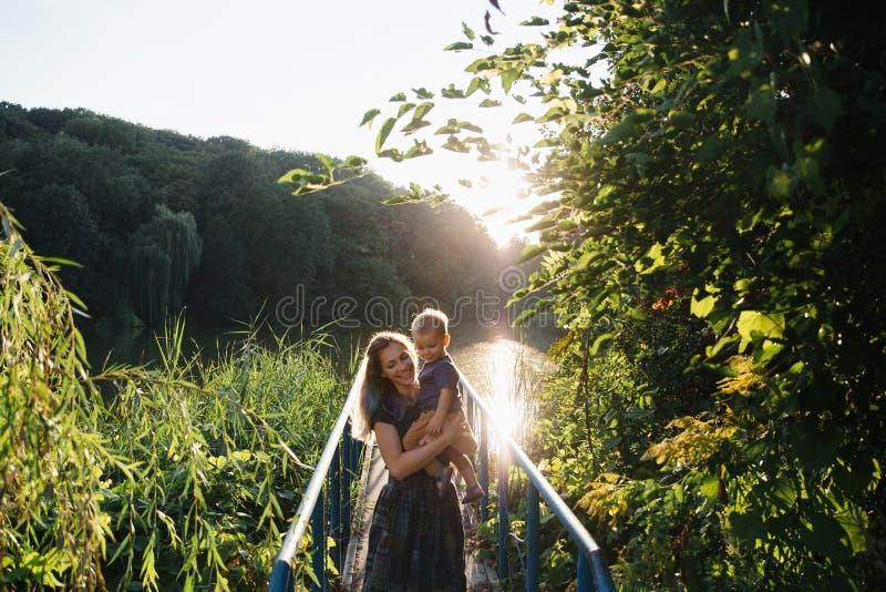 Vorderansichtmutter und Babysohn, der auf der Brücke auf See im Sommer Zeit glättend umarmt stockbild