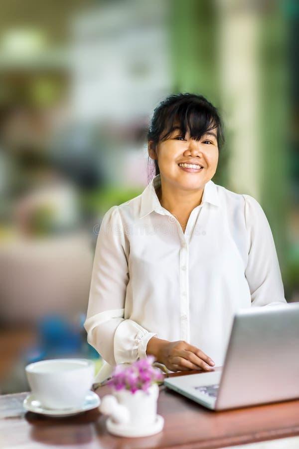 Vorderansichtporträt der glücklichen asiatischen Geschäftsfrau, die am langen Tisch in der Kaffeestube sitzt und Laptop-Computer  stockfotografie