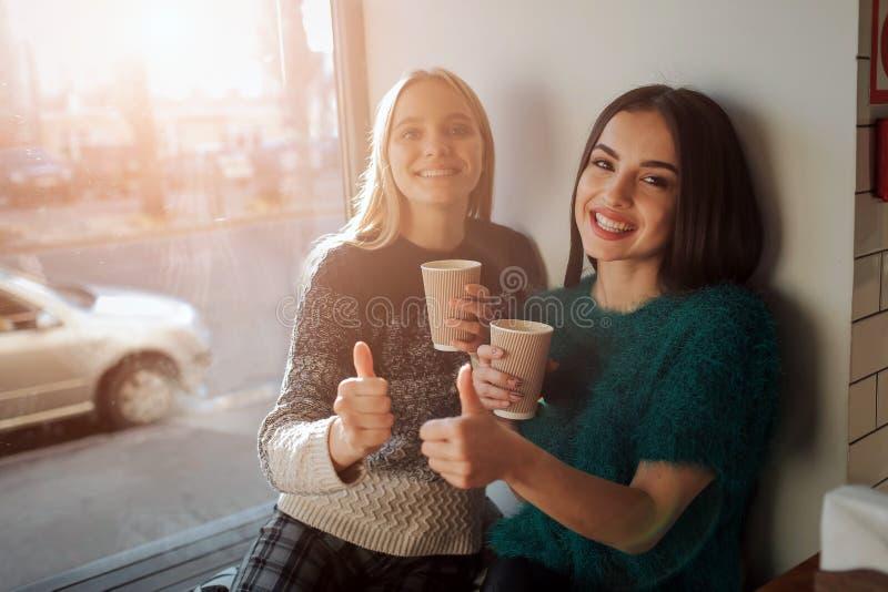 Vorderansichtporträt von zwei lustigen Freunden mit den Daumen up und schauend zur Kamera lizenzfreie stockfotos
