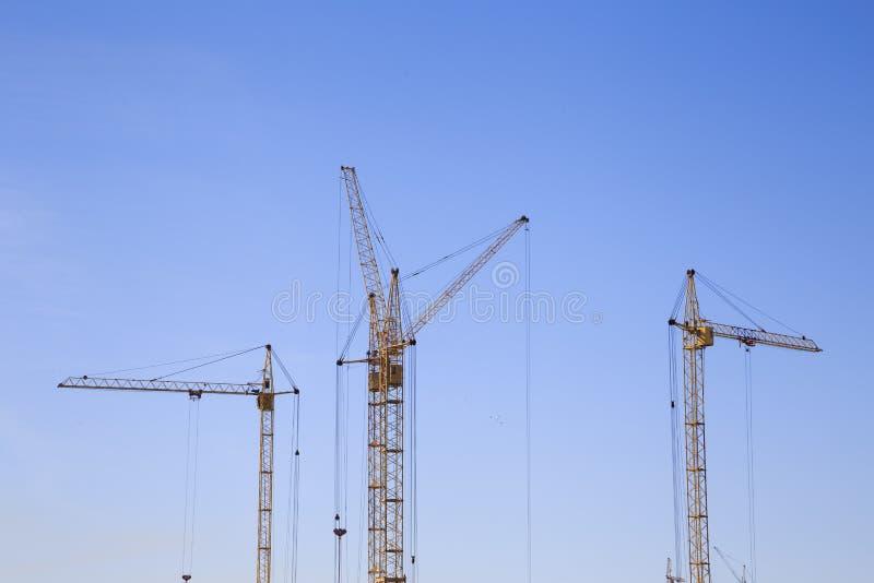 Vordere entfernte Ansicht von drei Kränen auf einem hellblauen Himmelhintergrund lizenzfreie stockfotos