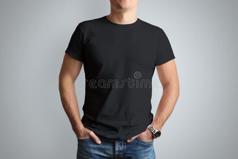 Vorderes Modellschwarzes T-Shirt auf einem jungen Kerl lokalisiert auf einem grauen Ba stockbild