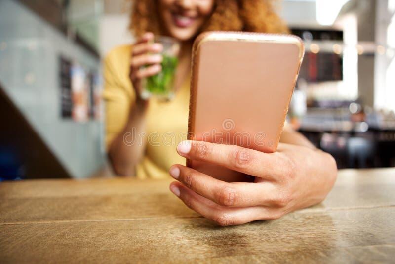 Vorderes Porträt der glücklichen jungen Frau, die am Café mit einem Getränk, Handy betrachtend sitzt lizenzfreies stockbild