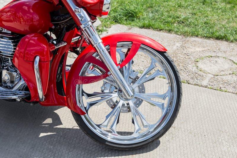 Vorderteil der Nahaufnahme des Retro- kundenspezifischen Motorrades Glänzendes Chromweinlese-Fahrradrad mit rotem Fender lizenzfreie stockbilder
