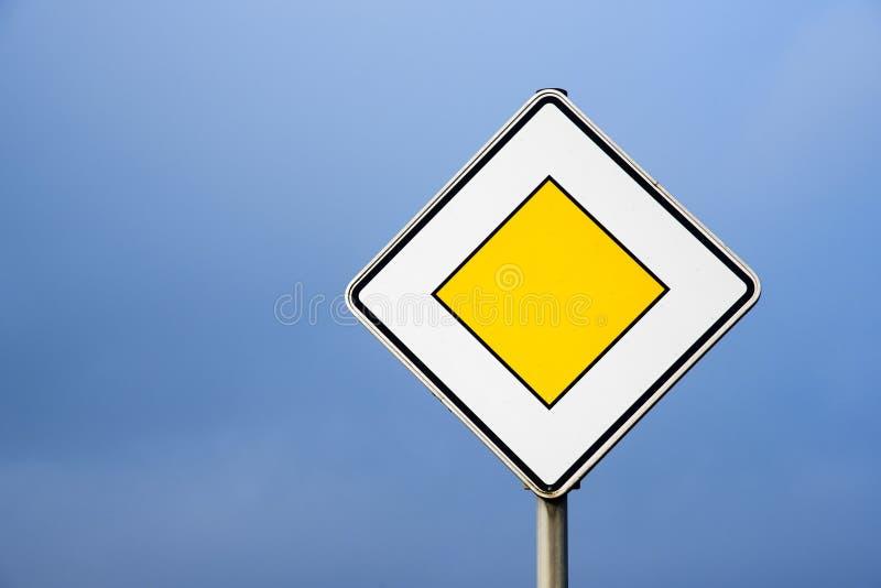 Vorfahrtsstraße, europäisches Verkehrszeichen gegen den klaren blauen Himmel lizenzfreie stockfotos