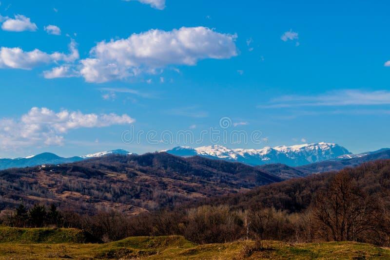 Vorfrühlingshügel mit Schnee umfassten Gebirgsspitzen im Hintergrund stockbild