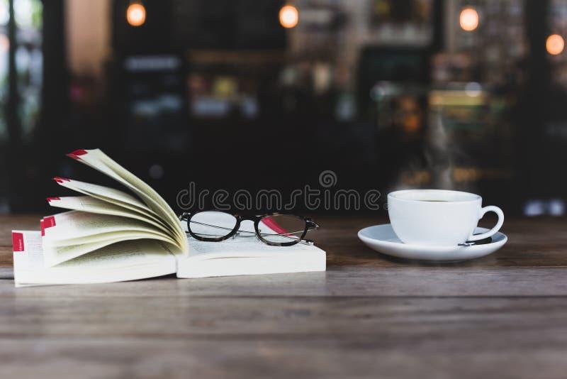 Vorgewählter Fokus der Kaffeetasse mit offenem Buch und Gläsern auf woode stockfotografie